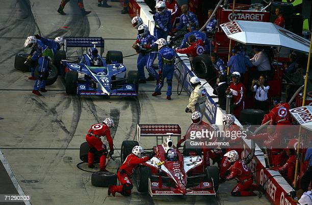 Scott Dixon driver of the Target Ganassi Racing Dallara Toyota and Dan Wheldon driver of the Target Ganassi Racing Dallara Honda make tire and fuel...