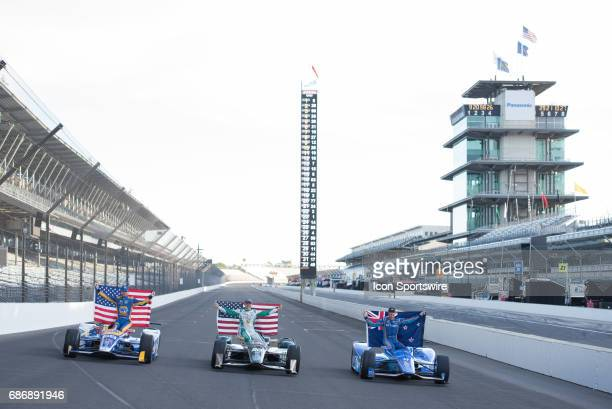Scott Dixon holing the New Zealand flag with fellow front row starters Ed Carpenter and Alexander Rossi holding American flags during the Front Row...