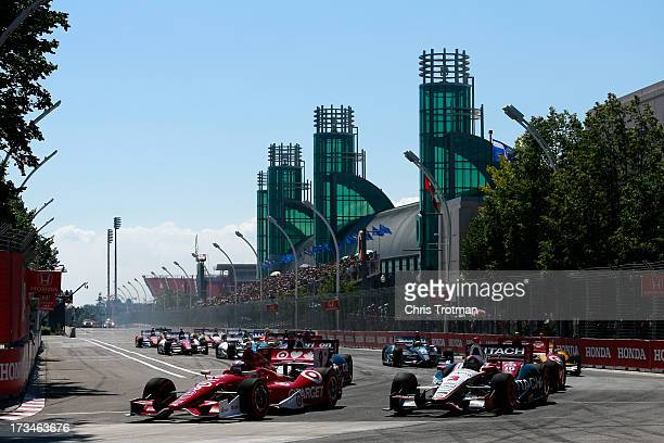 Scott Dixon of New Zealand driver of the Target Chip Ganassi Racing Honda leads Helio Castroneves of Brazil driver of the Hitatchi Team Penske...