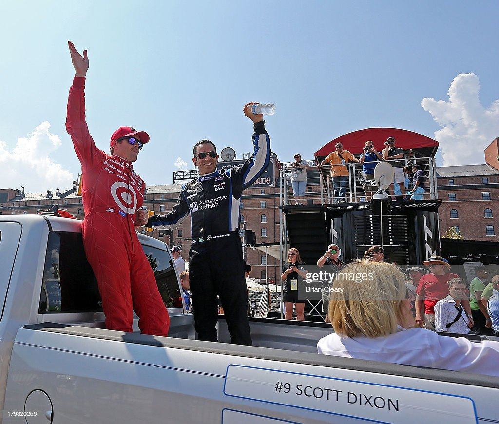 Scott Dixon of New Zealand (L), driver of the #9 Target Chip Ganassi Racing Honda Dallara and Helio Castroneves, of Brazil, driver of the #3 Team Penske Chevrolet Dallara wave to fans before the Grand Prix of Baltimore on September 1, 2013 in Baltimore, Maryland.