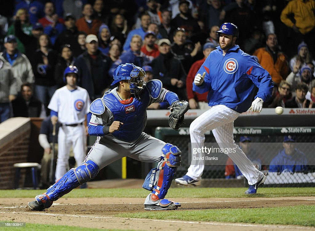 <a gi-track='captionPersonalityLinkClicked' href=/galleries/search?phrase=Scott+Feldman&family=editorial&specificpeople=540379 ng-click='$event.stopPropagation()'>Scott Feldman</a> #46 of the Chicago Cubs scores as <a gi-track='captionPersonalityLinkClicked' href=/galleries/search?phrase=Geovany+Soto&family=editorial&specificpeople=743668 ng-click='$event.stopPropagation()'>Geovany Soto</a> #8 of the Texas Rangers takes the throw during the fourth inning on May 6, 2013 at Wrigley Field in Chicago, Illinois.