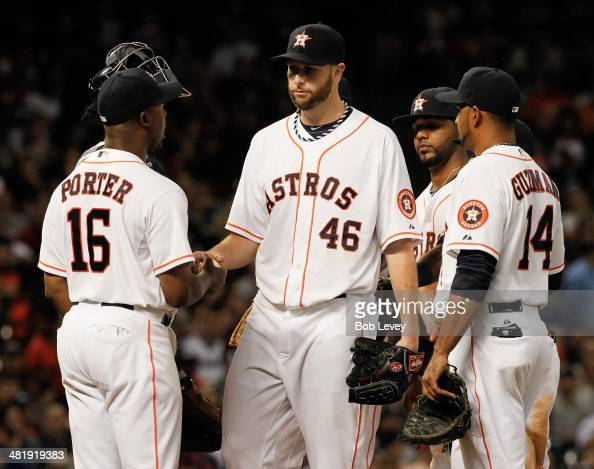 Scott Feldman of the Houston Astros hands the ball to manager manager Bo Porter as he leaves the game in the seventh inning as Jesus Guzman looks on...