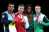 Scott Fitzgerald of England poses with silver medalist Mandeep Jangra of India and bronze medalists Tulani Mbenge of South Africa and Steven Donnelly...