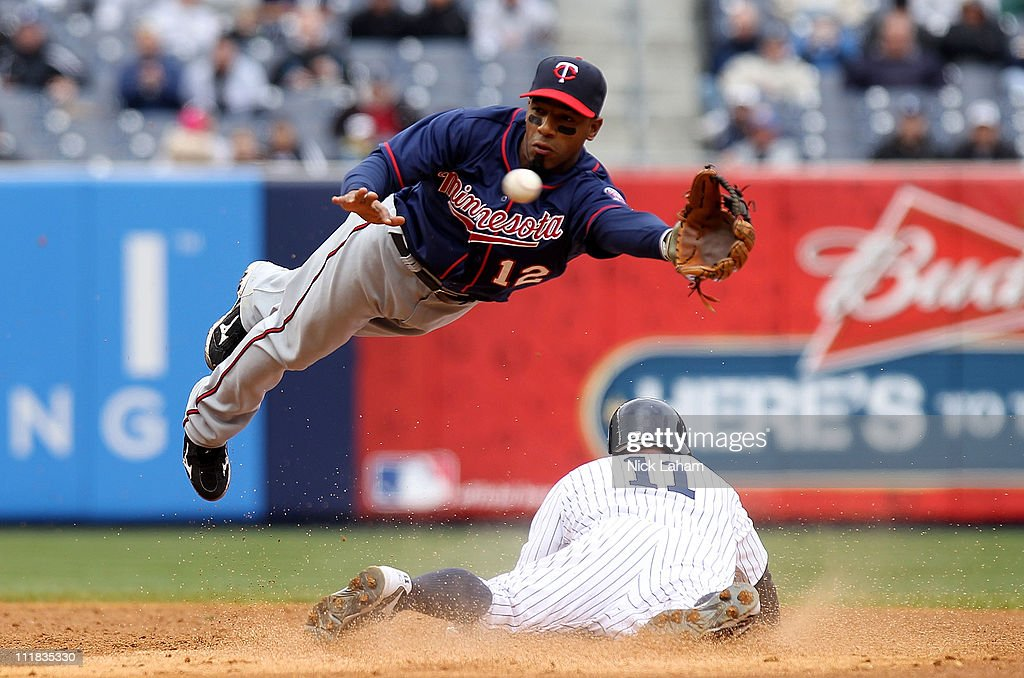 Scott Gardner of the New York Yankees safely slides into second base under Alexi Casilla of the Minnesota Twins at Yankee Stadium on April 7 2011 in...