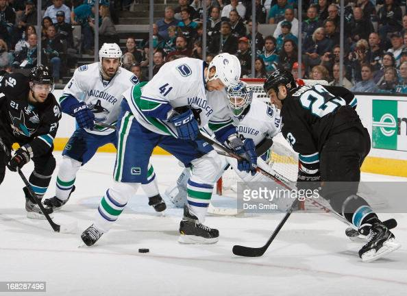 Scott Gomez and TJ Galiardi of the San Jose Sharks try to score against Cory Schneider Andrew Alberts and Jason Garrison of the Vancouver Canucks in...