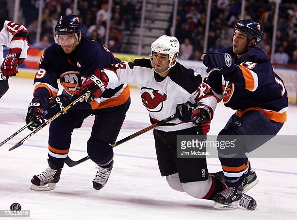 Scott Gomez of the New Jersey Devils reaches for the puck between Alexei Yashin and Chris Campoli of the New York Islanders during their NHL...
