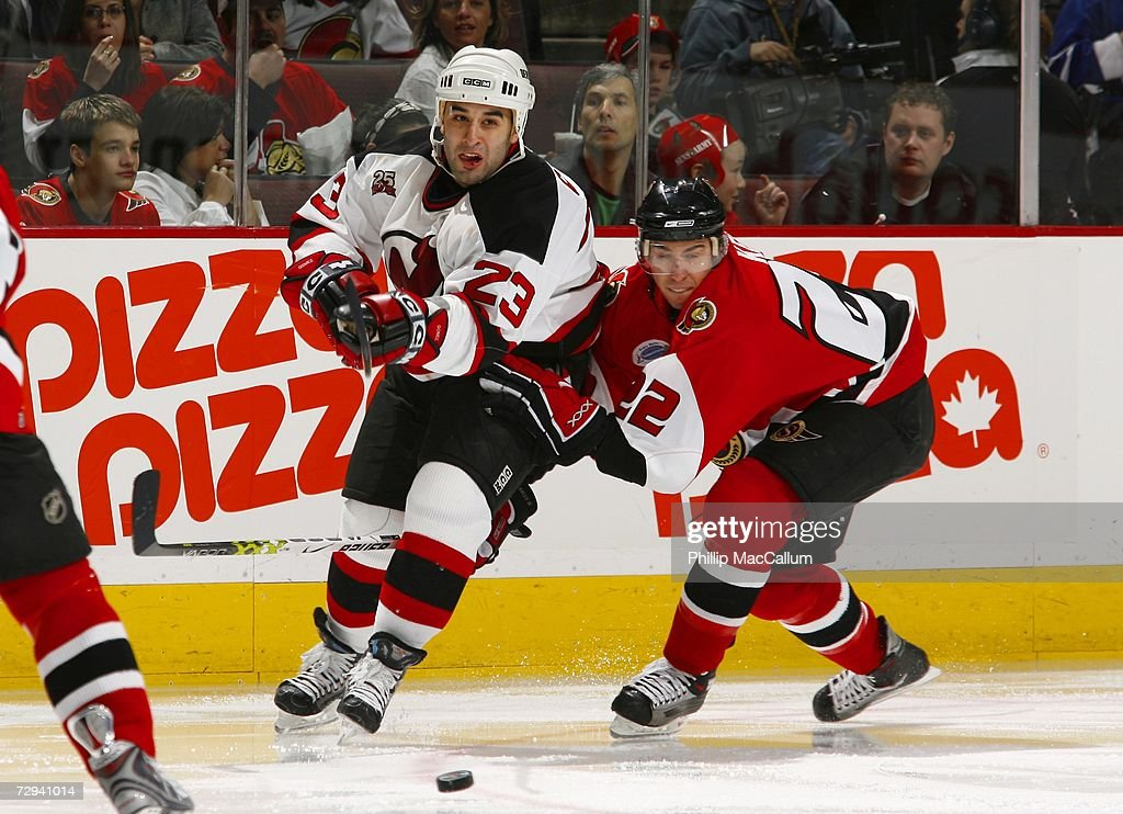 Scott Gomez of the New Jersey Devils tries to cut to the middle of the ice with the puck while fighting off the close checking of Chris Kelly of the...