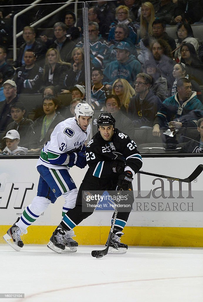 <a gi-track='captionPersonalityLinkClicked' href=/galleries/search?phrase=Scott+Gomez&family=editorial&specificpeople=201782 ng-click='$event.stopPropagation()'>Scott Gomez</a> #23 of the San Jose Sharks controls the puck taking it away from Dale Weise #32 of the Vancouver Canucks in the third period of their game at HP Pavilion on January 27, 2013 in San Jose, California. The Sharks won the game 4-1.