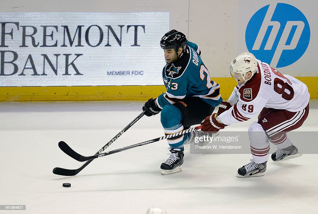 Scott Gomez #23 of the San Jose Sharks skates with control of the puck defended by Mikkel Boedker #89 of the Phoenix Coyotes at HP Pavilion on February 9, 2013 in San Jose, California.