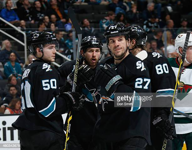 Scott Hannan Andrew Desjardins and Chris Tierney of the San Jose Sharks talk between plays against the Minnesota Wild during an NHL game on December...
