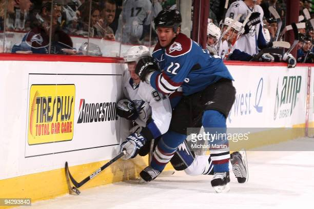 Scott Hannan of the Colorado Avalanche checks Steven Stamkos of the Tampa Bay Lightning into the boards at the Pepsi Center on December 11 2009 in...