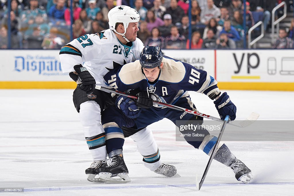 Scott Hannan of the San Jose Sharks and Jared Boll of the Columbus Blue Jackets battle for position during the first period on November 15 2014 at...