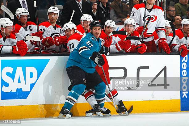 Scott Hannan of the San Jose Sharks checks Riley Nash of the Carolina Hurricanes into the boards at SAP Center on March 4 2014 in San Jose California