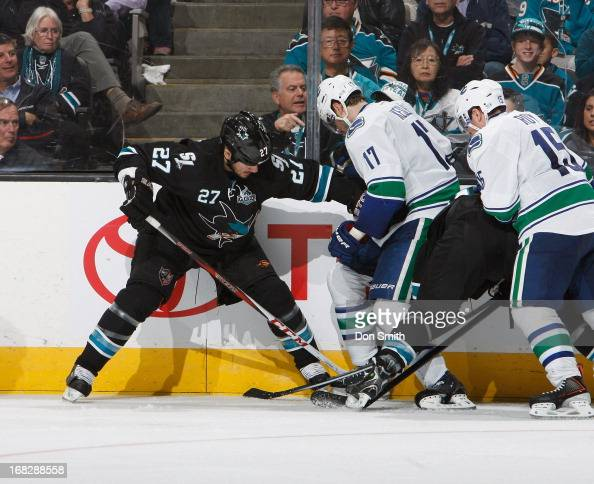 Scott Hannan of the San Jose Sharks fights for the puck against Ryan Kesler and Derek Roy of the Vancouver Canucks in Game Four of the Western...