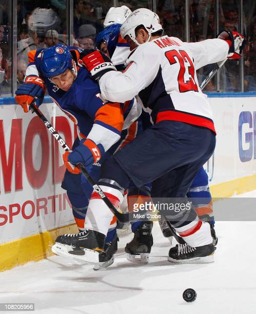 Scott Hannan of the Washington Capitals battles for the puck against Matt Martin of the New York Islanders on January 20 2011 at Nassau Coliseum in...