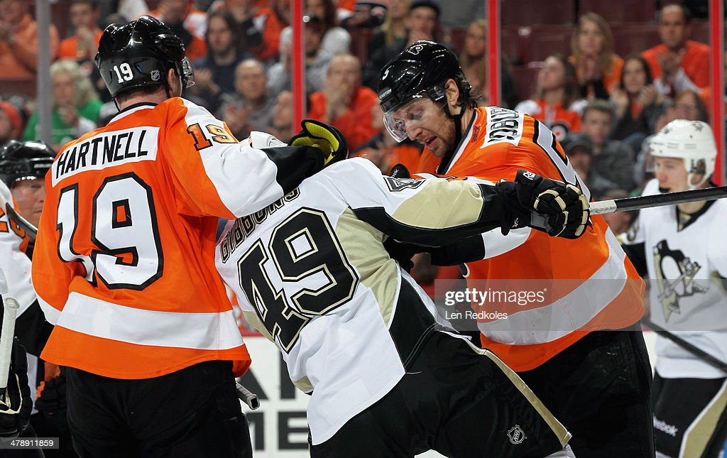 Scott Hartnel #19 and Braydon Coburn #5 of the Philadelphia Flyers scuffle with Brian Gibbons #49 of the Pittsburgh Penguins on March 15, 2014 at the Wells Fargo Center in Philadelphia, Pennsylvania.