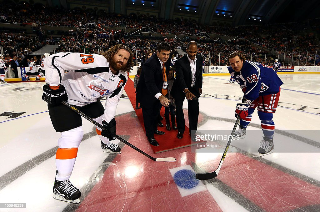 Scott Hartnell #19 (L) and Brad Richards #19 (R) take the ceremonial puck drop from Joe Watson (2nd-L), Caesars Entertainment VP of Nation Marketing, and Edward Dickson, Director New Jersey Office of Homeland Security during Operation Hat Trick Benefit Exhibition Hockey Game at Boardwalk Hall Arena on November 24, 2012 in Atlantic City, New Jersey.