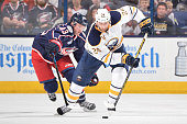 Scott Hartnell of the Columbus Blue Jackets attempts to knock the puck away from Tyson Strachan of the Buffalo Sabres during the second period on...