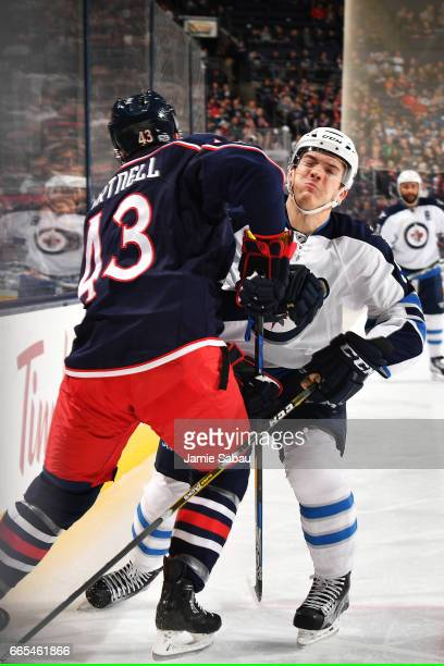 Scott Hartnell of the Columbus Blue Jackets collides with Jack Roslovic of the Winnipeg Jets during the first period of a game on April 6 2017 at...