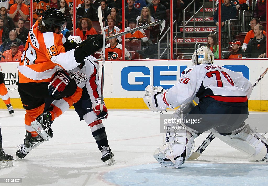 <a gi-track='captionPersonalityLinkClicked' href=/galleries/search?phrase=Scott+Hartnell&family=editorial&specificpeople=201889 ng-click='$event.stopPropagation()'>Scott Hartnell</a> #19 of the Philadelphia Flyers battles for position in front of goaltender <a gi-track='captionPersonalityLinkClicked' href=/galleries/search?phrase=Braden+Holtby&family=editorial&specificpeople=5370964 ng-click='$event.stopPropagation()'>Braden Holtby</a> #70 of the Washington Capitals with Steve Oleksy #61 on March 31, 2013 at the Wells Fargo Center in Philadelphia, Pennsylvania. The Flyers went on to defeat the Capitals 5-4 in overtime.