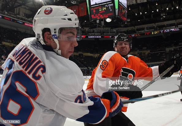 Scott Hartnell of the Philadelphia Flyers lines up Travis Hamonic of the New York Islanders at the Nassau Coliseum on December 5 2010 in Uniondale...