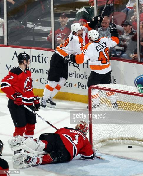 Scott Hartnell of the Philadelphia Flyers scores at 1546 of the second period against Johan Hedberg of the New Jersey Devils and is joined by Danny...