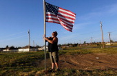 Scott Hasty places an American flag next to where his house was before it was destroyed by the massive tornado that passed through the town one year...