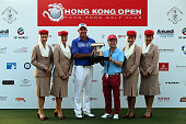 Scott Hend of Australia celebrates with his trophy and the Air Emirates official and the stewardess after winning the final round of the 2014 Hong...