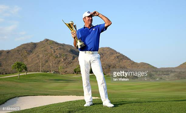 Scott Hend of Australia celebrates with the trophy after claiming victory during the final round on day four of the Thailand Classic at Black...