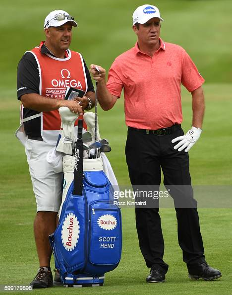 Scott Hend of Australia consults his caddy on the 17th hole during the final round of the Omega European Masters at CranssurSierre Golf Club on...