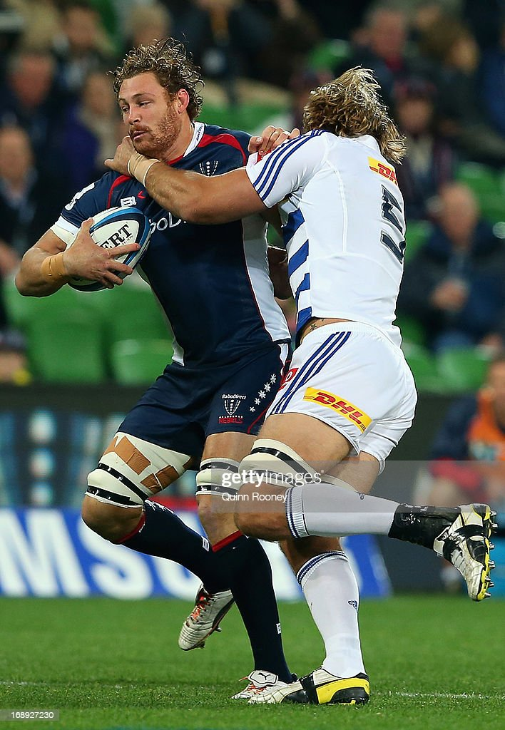 Scott Higginbotham of the Rebels is tackled by Andries Bekker of the Stormers during the round 14 Super Rugby match between the Rebels and the...