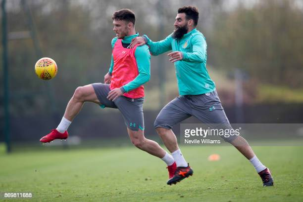 Scott Hogan of Aston Villa in action with team mate Mile Jedinak during a training session at the club's training ground at Bodymoor Heath on...