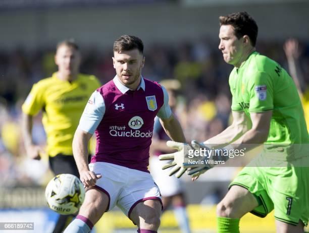 Scott Hogan of Aston Villa is challenged by Jon McLaughlin of Burton Albion during the Sky Bet Championship match between Burton Albion and Aston...