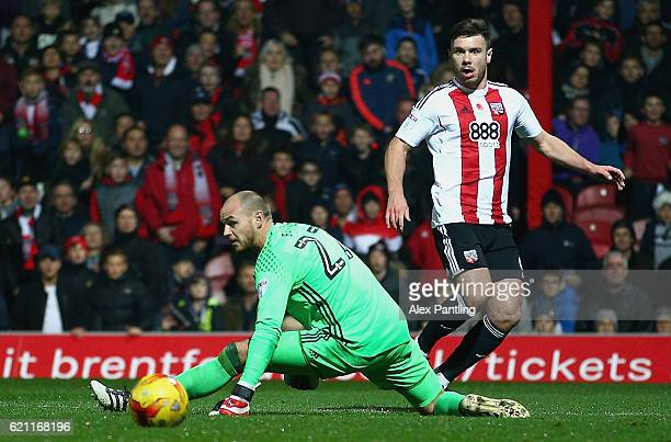 Scott Hogan of Brentford shoots wide as David Button of Fulham attempts to save during the Sky Bet Championship match between Brentford and Fulham at...