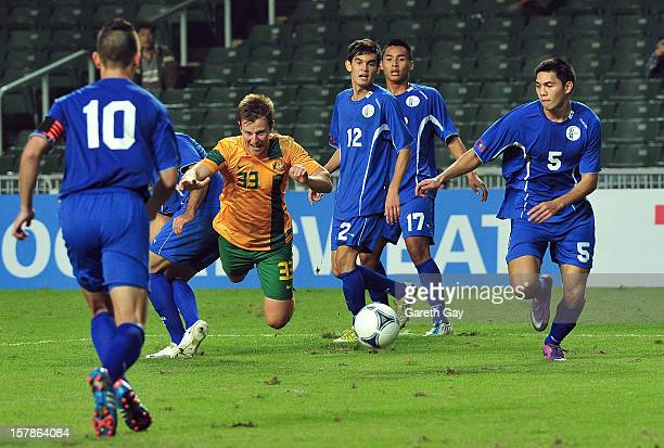 Scott Jamieson of Australia is tackled during the EAFF East Asian Cup 2013 Qualifying match between Guam and Australia at Hong Kong Stadium on...