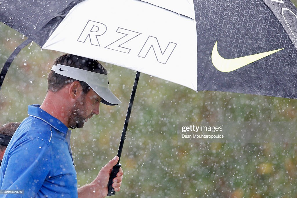 Scott Jamieson of Scotland shelters from the rain under his umbrella after he hits his tee shot on the 1st hole during Day 1 of the Portugal Masters...