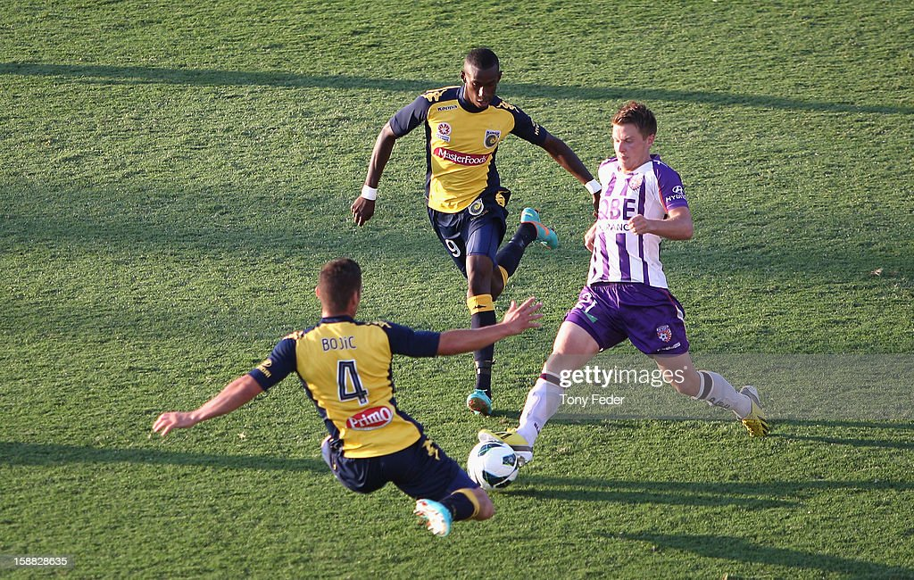 Scott Jamieson of the Glory contests the ball with Pedj Bojic and Bernie Ibini of the Mariners during the round 14 A-League match between the Central Coast Mariners and the Perth Glory at Bluetongue Stadium on December 31, 2012 in Gosford, Australia.