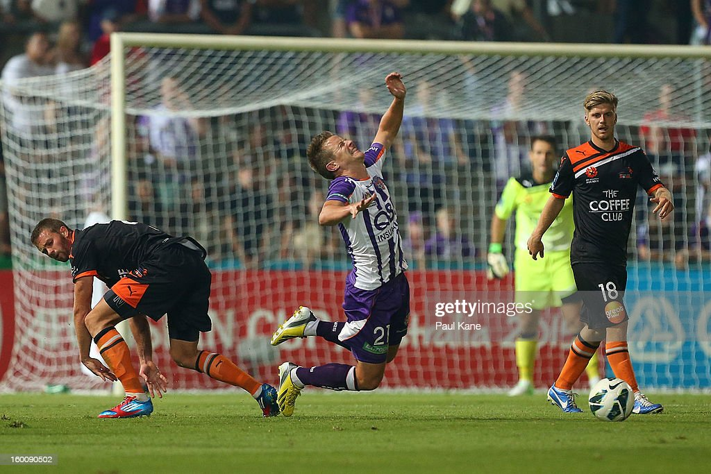 Scott Jamieson (C) of the Glory falls to the ground after being tackled by James Meyer of the Roar during the round 18 A-League match between the Perth Glory and the Brisbane Roar at nib Stadium on January 26, 2013 in Perth, Australia.
