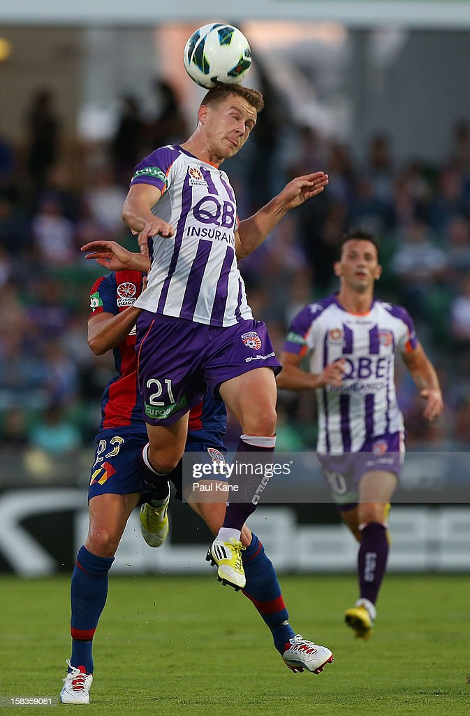 Scott Jamieson of the Glory heads the ball gainst Ryan Griffiths of the Jets during the round 11 ALeague match between the Perth Glory and the...