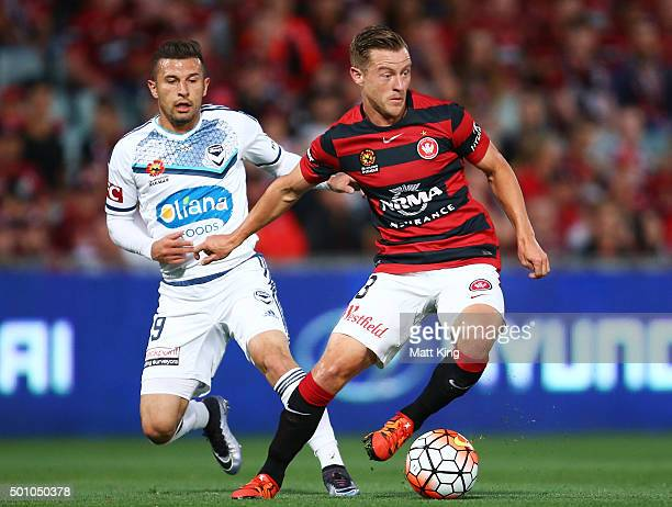 Scott Jamieson of the Wanderers is challenged by Kosta Barbarouses of Melbourne Victory during the round 10 ALeague match between the Western Sydney...
