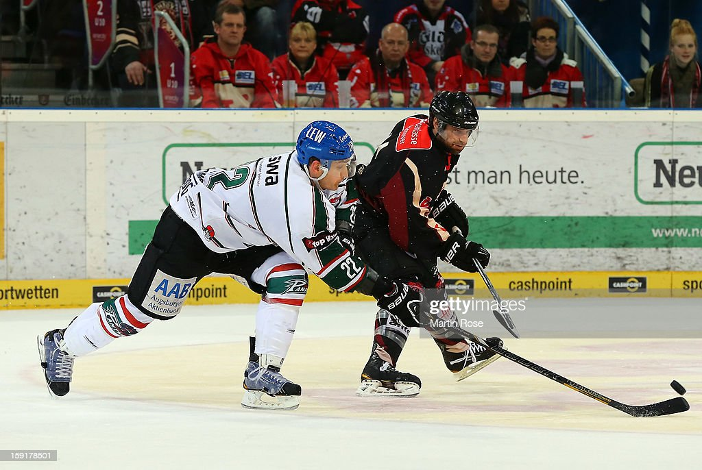 Scott King (R) of Hannover and Michael Bakos (L) of Augsburg battle for the puck during the DEL match between Hannover Scorpions and Augsburger Panther at TUI Arena at TUI Arena on January 9, 2013 in Hanover, Germany.