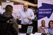 Scott Krewatch a recruiter for Compass Group speaks with a veteran at a 'Hiring our Heroes' Job Fair on March 27 2014 in New York City The jobs fair...
