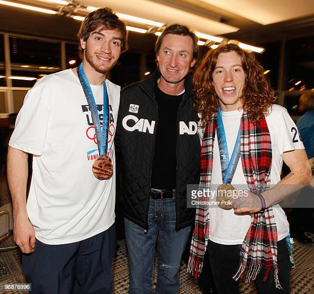 Scott Lago and Shaun White of the United States snowboard team pose with hockey great Wayne Gretzky and their Olympic medals at the USA House on...