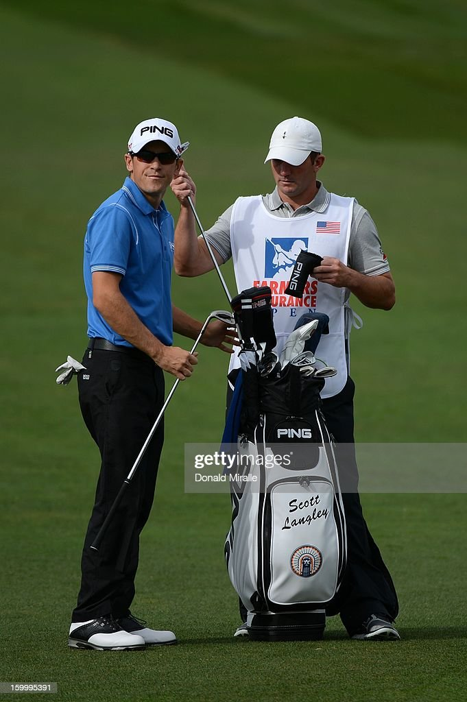 Scott Langley switches clubs with his caddie on the fairway on the ninth hole during the first round at the Farmers Insurance Open at Torrey Pines Golf Course on January 24, 2013 in La Jolla, California.