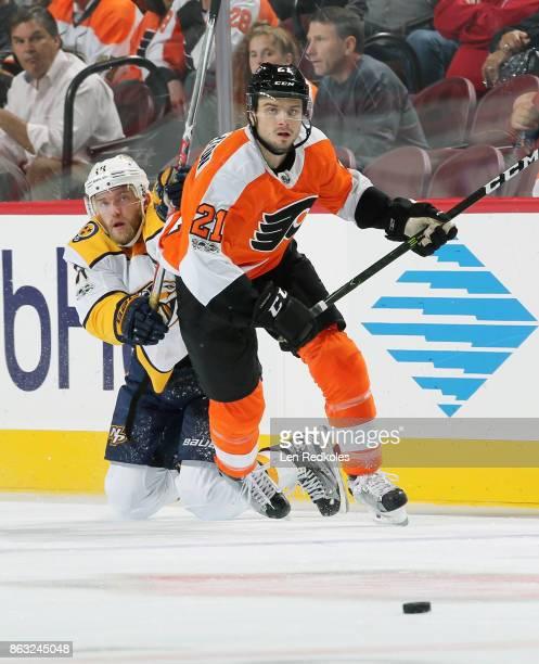Scott Laughton of the Philadelphia Flyers and Mattias Ekholm of the Nashville Predators pursue the loose puck on October 19 2017 at the Wells Fargo...