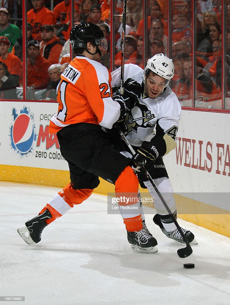 Scott Laughton #21 of the Philadelphia Flyers checks Simon Despres #47 of the Pittsburgh Penguins off of the puck on January 19, 2013 at the Wells Fargo Center in Philadelphia, Pennsylvania.
