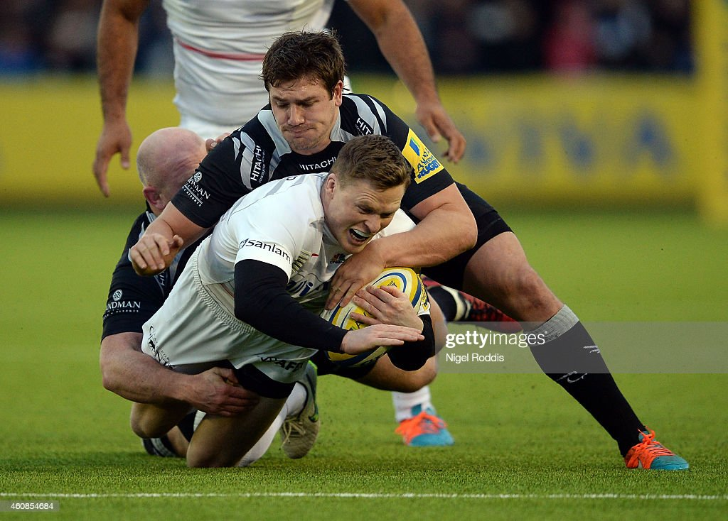 Scott Lawson and Adam Powell of Newcastle Falcons tackle Chris Ashton of Saracens during the Aviva Premiership match between Newcastle Falcons and...