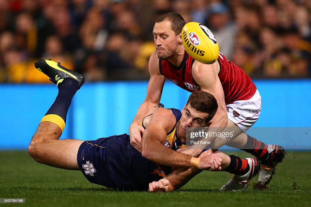 Scott Lycett of the Eagles gets his handball away while being tackled by James Kelly of the Bombers during the round 15 AFL match between the West Coast Eagles and the Essendon Bombers at Domain Stadium on June 30, 2016 in Perth, Australia.
