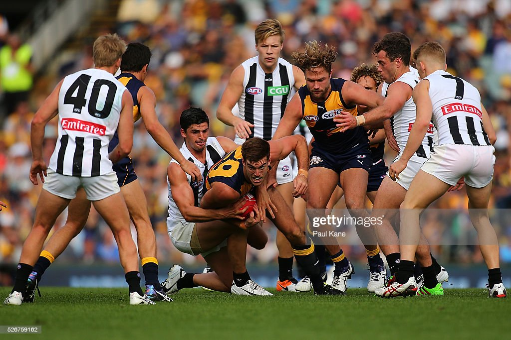Scott Lycett of the Eagles looks to handball while being tackled during the round six AFL match between the West Coast Eagles and the Collingwood Magpies at Domain Stadium on May 1, 2016 in Perth, Australia.