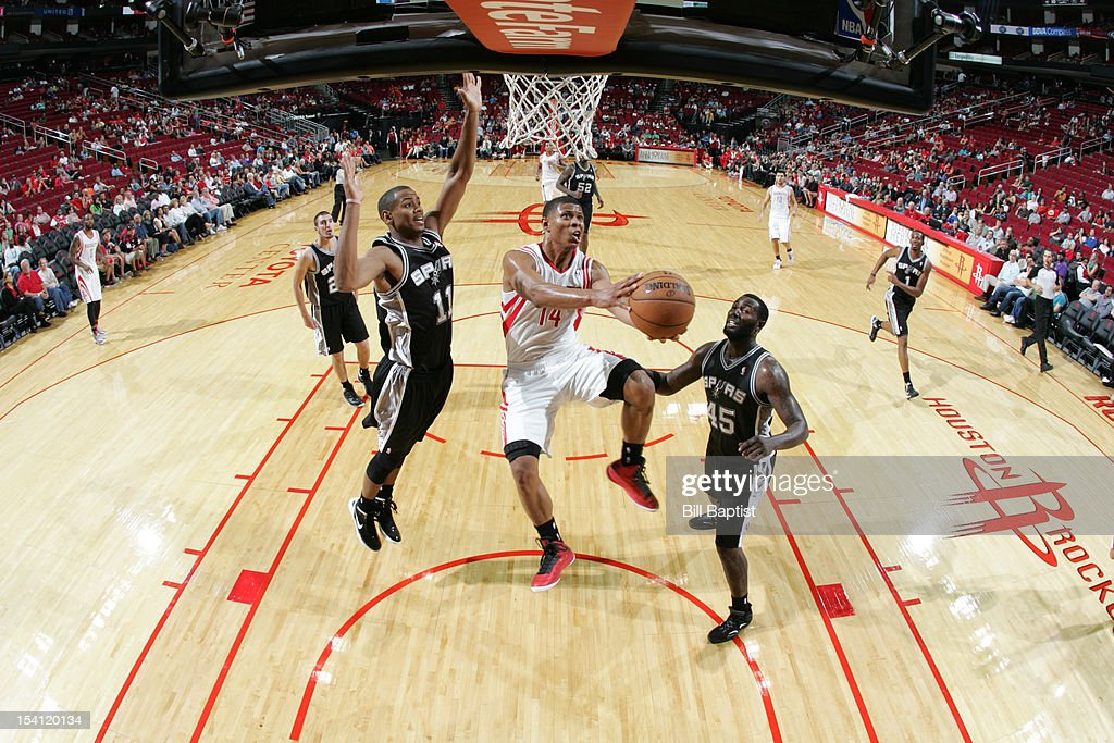 Scott Machado #14 of the Houston Rockets shoots the ball over Wesley Witherspoon #11 and <a gi-track='captionPersonalityLinkClicked' href=/galleries/search?phrase=DeJuan+Blair&family=editorial&specificpeople=4649451 ng-click='$event.stopPropagation()'>DeJuan Blair</a> #45 of the San Antonio Spurs during a pre-season game on October 14, 2012 at the Toyota Center in Houston, Texas.